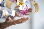 Hand wirft Euroschein in die Luft