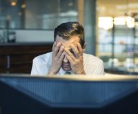 Mann sitzt verzweifelt vor Rechner
